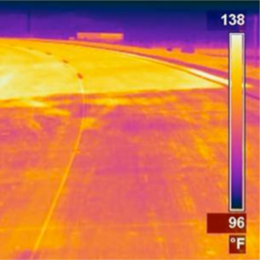 Thermal infrared image of a road with light and dark segments.