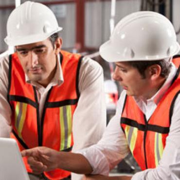Two men wearing hard hats and orange vests in front of a laptop